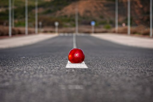Perfect road with a red apple placed on the white line laid by road construction companies