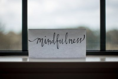 """Piece of paper that reads """"mindfulness"""" on a window sill to remind us to let things go"""