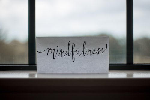 "Piece of paper that reads ""mindfulness"" on a window sill to remind us to let things go"