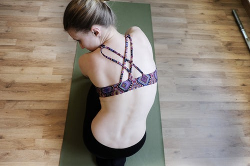 Woman kneeling on yoga matt to try and let things go